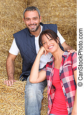 Farmer and wife sitting on hay