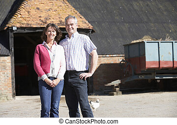 Farmer And Wife Standing In Front Of Farm Buildings