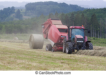 Farmer baling hay in a misty mountain pasture - Farmer...