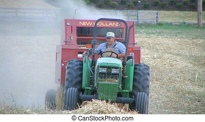 Farmer Baling Hay - Farmer round baling hay.