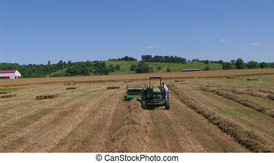 Farmer Baling Hay - Farmer baling hay with accumulator,...