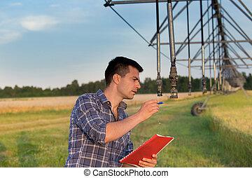 Farmer beside irrigation system in field