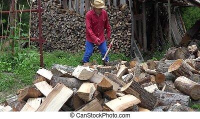 Farmer boy chopping wood in backyard. 4K