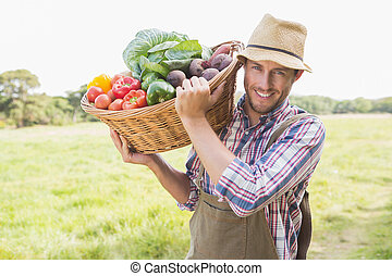 Farmer carrying basket of veg on a sunny day