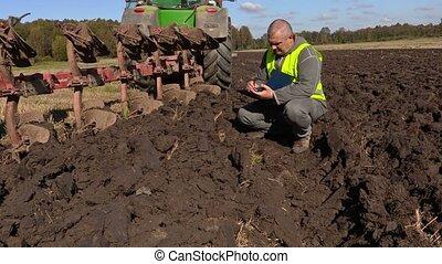 Farmer checking plowed soil