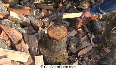 Farmer chopping wood outdoors - Farmer chopping firewood...