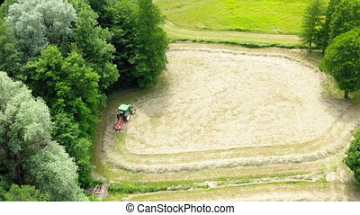 Farmer in tractor harvesting hay on the grass field with green forest around, aerial view