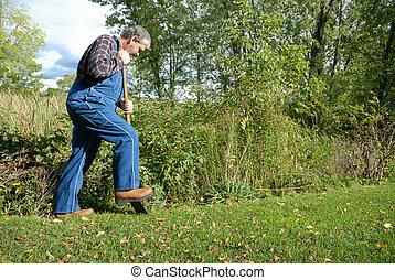 bearded farmer, wearing bib overalls & plaid shirt digging in meadow