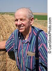 Elderly farmer in front of his field