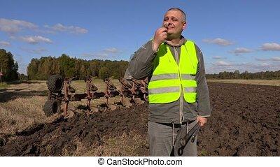 Farmer enjoy chamomile flower near plow on field