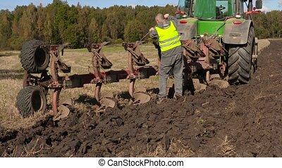 Farmer fixing bolts on plow near tractor