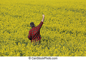 Farmer gesturing in blossoming rapeseed field