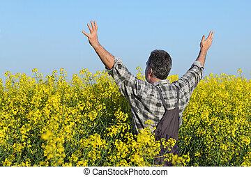 Farmer gesturing in rapeseed field