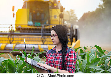 Farmer girl on field with combine harvester - Young pretty...