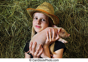 Farmer girl with a little baby piglet