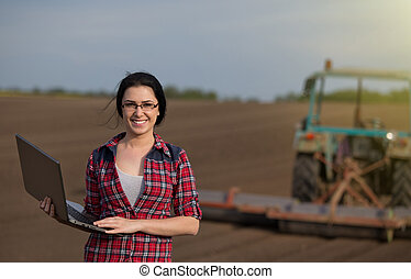 Farmer girl with laptop in field with tractor - Young happy ...