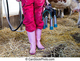 Farmer girl with milking machine in stable