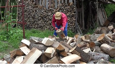 Farmer guy chops wood near woodshed. 4K