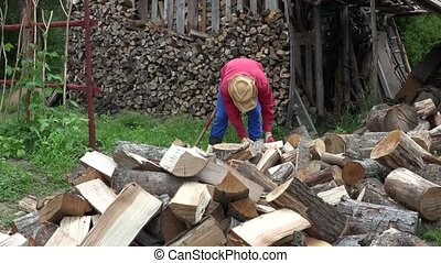 Farmer guy prepare organic wood fuel near woodshed for winter season. 4K