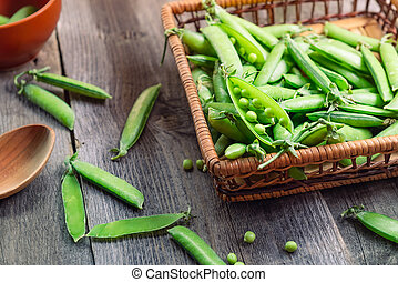 Farmer Harvest of fresh green peas on the table and in a woven straw basket on the old rustic wooden background. Top view, selective focus. Space for text.