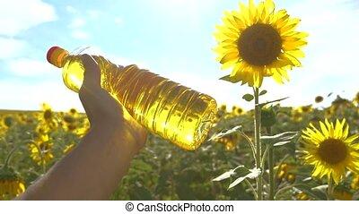 farmer holding a plastic bottle lifestyle of sunflower oil...