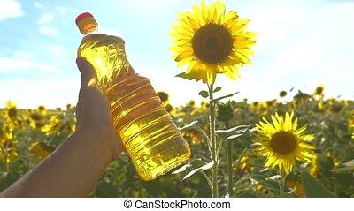 farmer holding a plastic bottle of sunflower lifestyle oil...