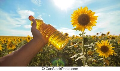 farmer holding a plastic bottle of sunflower oil in his hand field sunlight. slow motion video. blue sky background agriculture concept sunflower oil bottle farming sunset field lifestyle