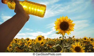 farmer holding a plastic bottle of sunflower oil in his hand field sunlight. slow motion video. blue sky background agriculture concept sunflower oil bottle lifestyle farming sunset field