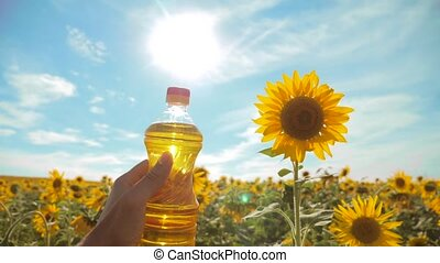 farmer holding a plastic bottle of sunflower oil in his hand field sunlight. slow motion video. blue sky background agriculture concept sunflower oil lifestyle bottle farming sunset field