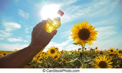 farmer holding a plastic bottle of sunflower oil in his hand field sunlight. slow motion video. blue sky background agriculture concept sunflower oil bottle farming lifestyle sunset field