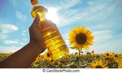farmer holding a plastic bottle of sunflower oil in his hand field sunlight. slow motion video. blue sky background agriculture concept sunflower lifestyle oil bottle farming sunset field