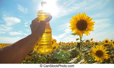 farmer holding a plastic bottle of sunflower oil in his hand field sunlight. slow motion video. blue sky background agriculture concept sunflower oil bottle farming sunset lifestyle field