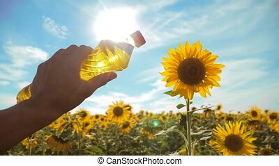 farmer holding a plastic bottle of sunflower oil in his hand field sunlight. slow motion video. blue sky background agriculture lifestyle concept sunflower oil bottle farming sunset field