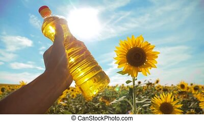 farmer holding a plastic bottle of sunflower oil in his hand field sunlight. slow motion video. blue sky background agriculture concept lifestyle sunflower oil bottle farming sunset field
