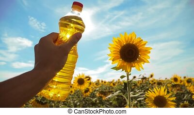 farmer holding a plastic bottle of sunflower oil in his hand field sunlight. slow motion video. blue sky lifestyle background agriculture concept sunflower oil bottle farming sunset field