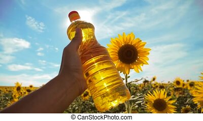 farmer holding a plastic bottle of sunflower oil in his hand field sunlight. slow motion video. lifestyle blue sky background agriculture concept sunflower oil bottle farming sunset field