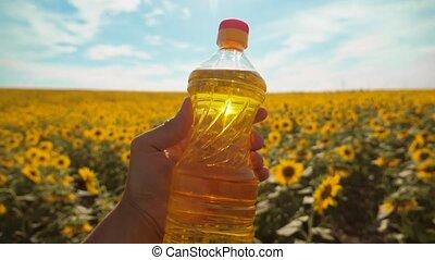 farmer holding a plastic bottle of sunflower oil in his...