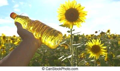 farmer holding a plastic bottle of sunflower oil lifestyle...