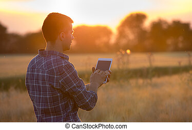 Farmer holding tablet in field at sunset