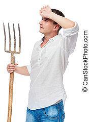 Farmer in a white shirt with a pitchfork in his hand wiping the sweat from his forehead is isolated