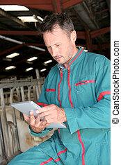 Farmer in barn using electronic tablet