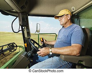 Farmer in combine. - Farmer driving combine and harvesting...