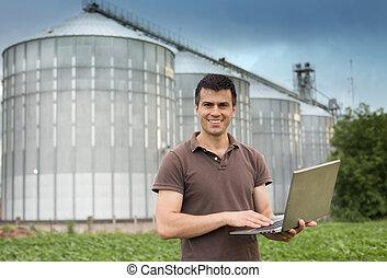 Farmer in front of grain silo