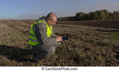 Farmer in middle of the field with a tablet pc