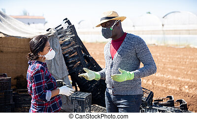 Farmer in protective mask gives assignment to hired worker