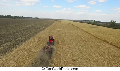 Farmer in red tractor preparing land for sowing. aerial shot
