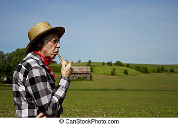 farmer in straw hat with corn cob pipe