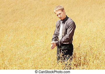 Farmer in suit standing in field of oats
