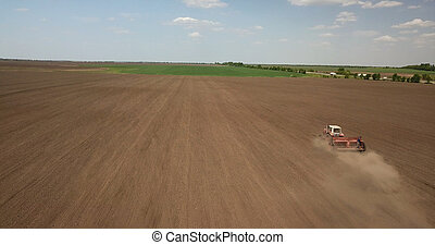 Farmer in tractor preparing land with seedbed cultivator against the blue sky