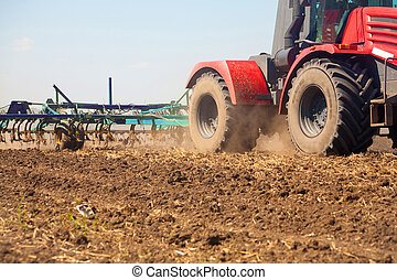 Farmer in tractor preparing land with seedbed cultivator - ...